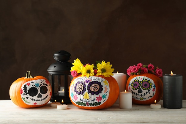 Pumpkins with catrina skull makeup and halloween accessories on brown background