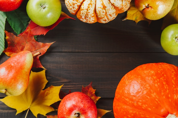 Pumpkins with colorful maple leaves, ripe apples and pear on dark wooden background