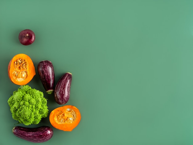 Pumpkins with eggplants and romanesco cabbage on green background