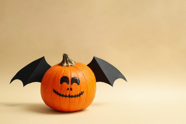 Pumpkins with smile and wings on beige