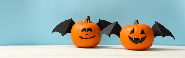 Pumpkins with smile and wings on blue background