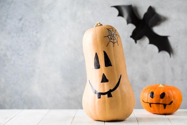 Тыквы с жуткими лицами на столе на праздновании хэллоуина