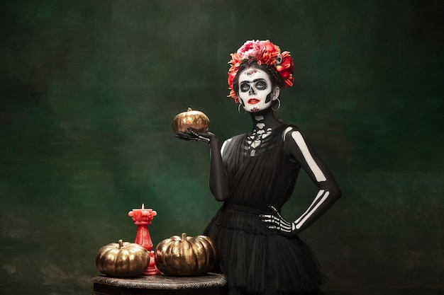 Pumpkins. young girl like santa muerte saint death or sugar skull with bright make-up. portrait isolated on dark green studio background with copyspace. celebrating halloween or day of the dead.