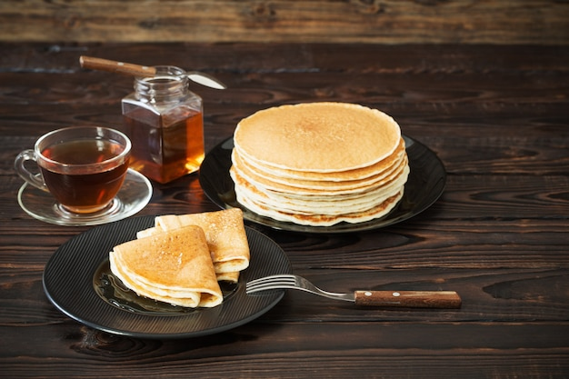 오래된 나무 배경에 꿀과 차 한 잔을 넣은 펀케이크