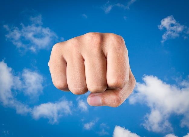 흐릿한 추상 파란색과 흐린 하늘 배경에 주먹을 날립니다.