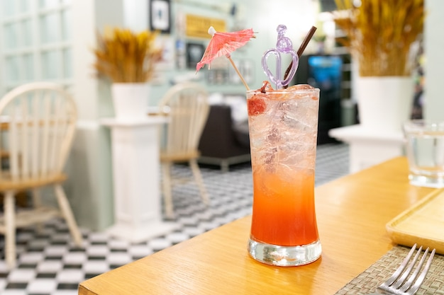 Punch soda on wooden table with restaurant background