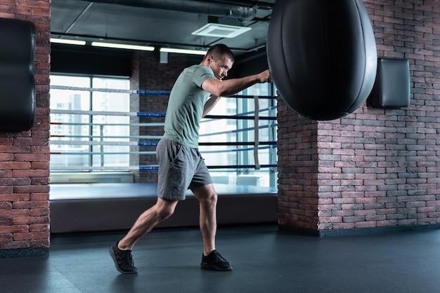 Punching bag. skillful dark-haired professional boxer beating punching bag while training hard in gym