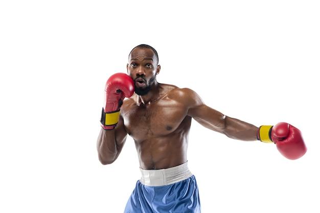 パンチング。白いスタジオの背景に分離されたプロのアフリカ系アメリカ人ボクサーの面白い、明るい感情。ゲームの興奮、人間の感情、顔の表情、スポーツコンセプトへの情熱。