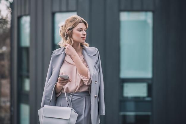 時間厳守。通りで会うのを待っているハンドバッグとスマートフォンと灰色のスーツのブロンドのウェーブのかかった髪を持つ美しい実業家