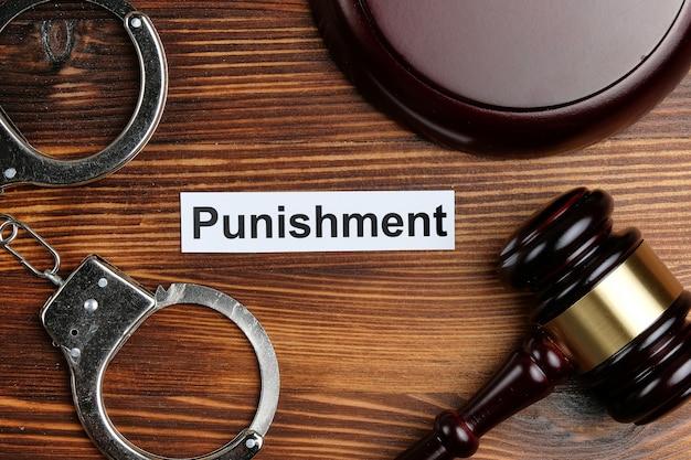 Концепция наказания на наклейке рядом с наручниками и молотком судьи.