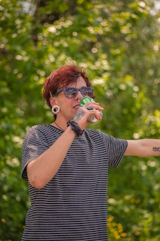 Punk boy drinks beer outdoors with trees in background