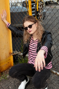 Femmina punk con occhiali da sole in posizione urbana