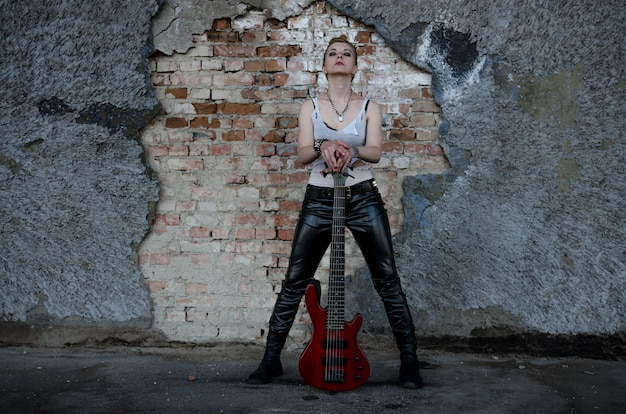 Punk girl dressed in black leather pants and white shirt, with red bass guitar at abadoned place