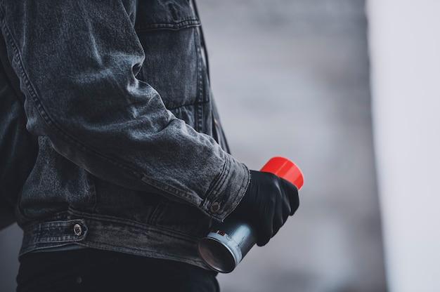 Панк в джинсовой куртке и черных перчатках принимает аэрозольную краску. новые субкультуры на городских улицах