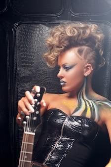 Панк женщина с бас-гитарой кожаной тканью яркий боди-арт