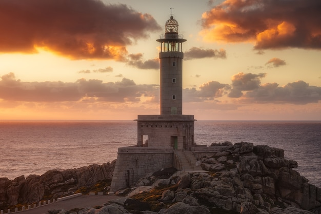 Punta nariga lighthouse in galicia, spain at sunset