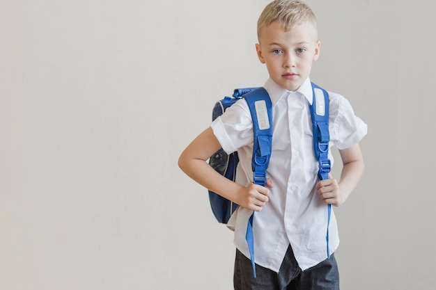 Pupil in backpack standing in studio