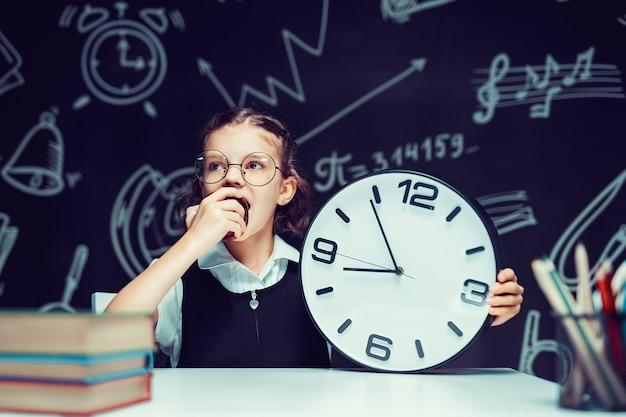 教室の黒い黒板でリンゴを食べる大きな時計を持つ瞳孔の女の子