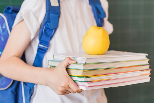 Pupil holding textbooks and apple