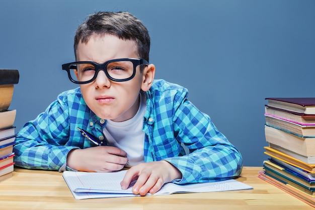Ученик в очках прищуривается, концепция плохого зрения. молодой школьник сидит за партой против множества книг