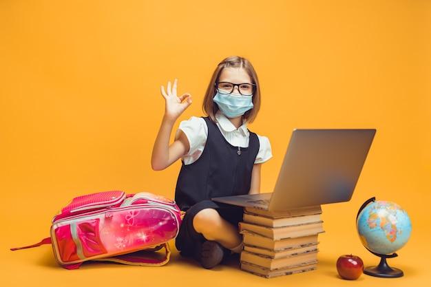 의료 마스크를 쓴 학생은 책 더미 뒤에 앉아 있고 노트북 제스처는 괜찮은 아이들 교육입니다.