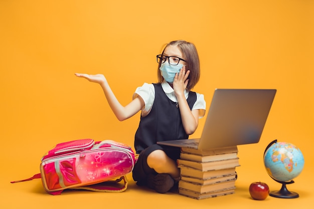 의료 마스크를 쓴 학생은 책 더미 뒤에 앉아 있고 노트북은 빈 공간 어린이 교육을 가리킵니다.