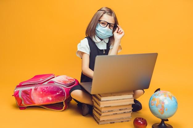 의료용 마스크를 쓴 학생은 전염병 속에서 노트북 어린이 교육에 관한 책 더미 뒤에 앉아 있다