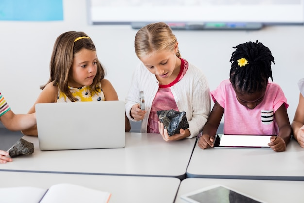 Pupil looking at rock with magnifying glass and classmates using technology