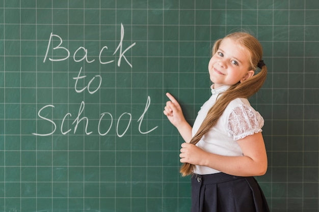Pupil pointing at back to school inscription on chalkboard
