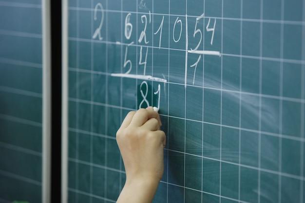 生徒の手は黒板のチョーク番号に書き込み、数学的なタスクを解決します