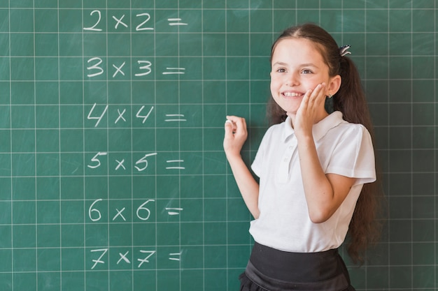 Pupil standing near blackboard with calculations