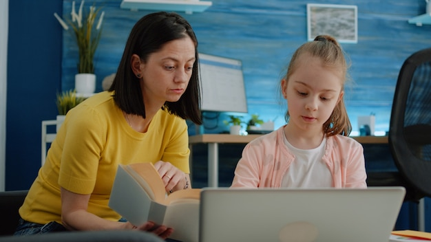Pupil using laptop and notebook for homework with help from mother
