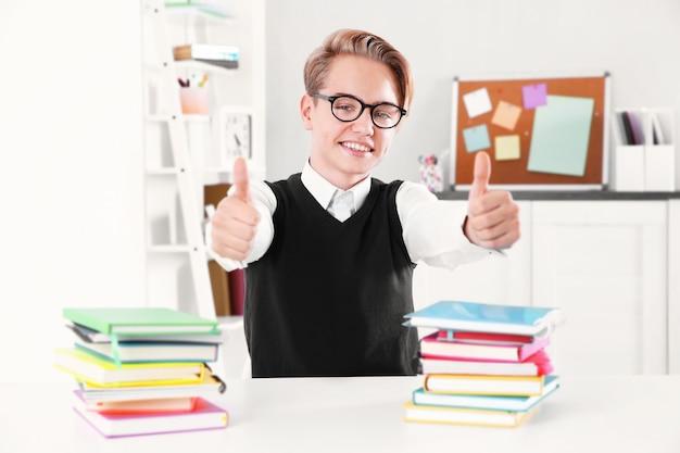教室の机に座っている本の山を持つ生徒