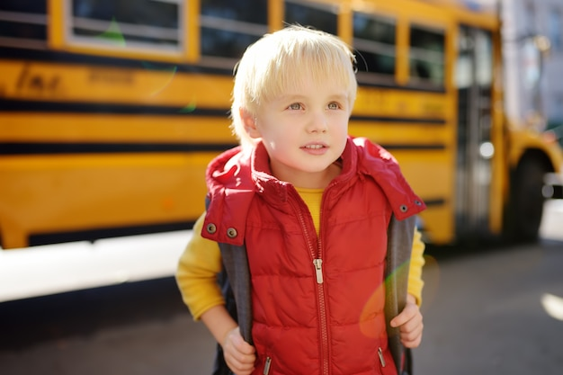 Pupil with schoolbag with yellow school bus on background.