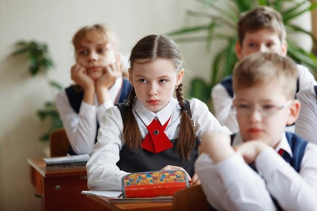 机の上の生徒は学校での仕事を考えて決定します。初等教育、訓練および人々の概念