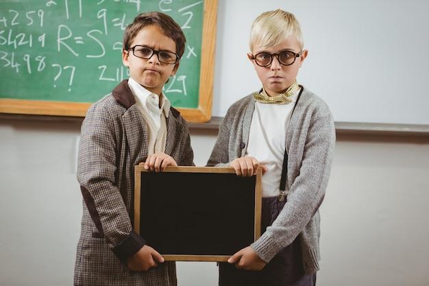 Pupils dressed up as teachers holding chalkboard