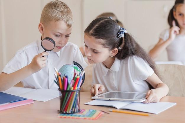 Учащиеся, изучающие глобус на уроке