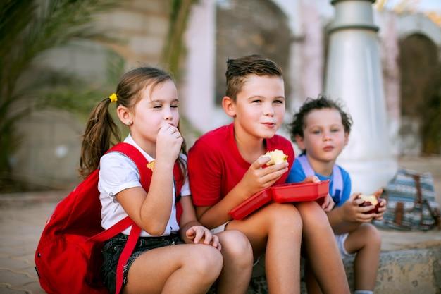 야외에서 간식을 먹는 학생. 어린이, 교육 및 영양 개념