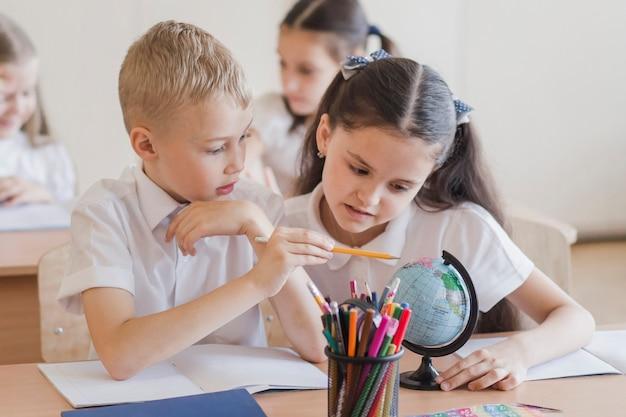 Ученики, смотрящие на глобус вместе