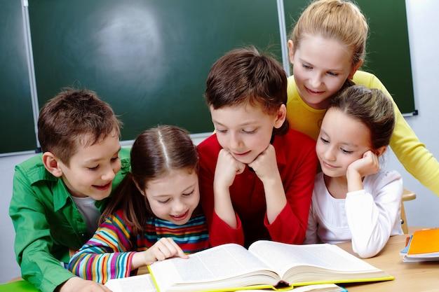 面白い本のページを見ている生徒