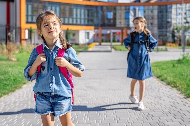 小学校の生徒。屋外の建物の近くにバックパックを持った女の子。レッスンの始まり。秋の初日。