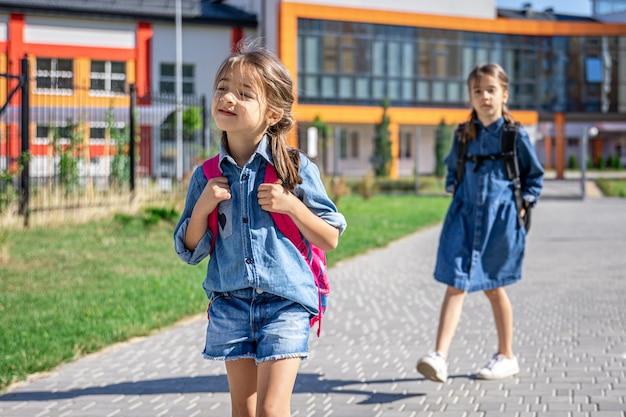 小学校の生徒。屋外の学校の近くのバックパックを持つ女の子。レッスンの始まり。秋の初日。