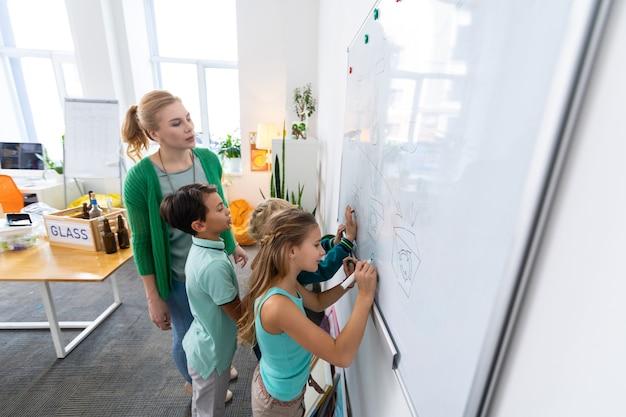 Рисование школьников. ученики чувствуют себя вовлеченными в рисование различных видов мусора на белой доске.