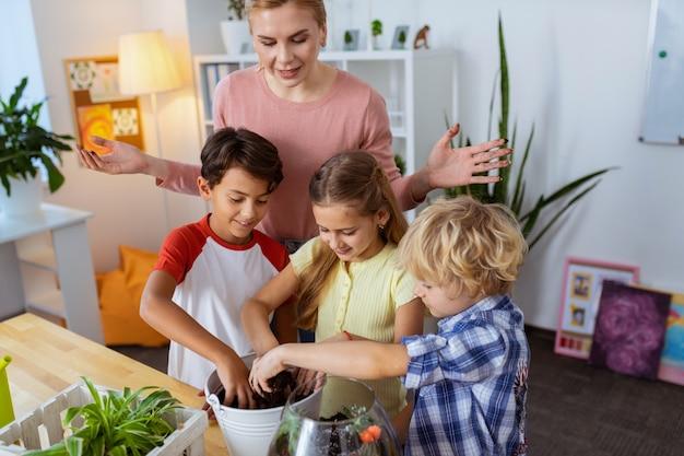 Ученики горшечных растений. учительница очень счастлива, видя, как ее ученики сажают растения на уроке ботаники
