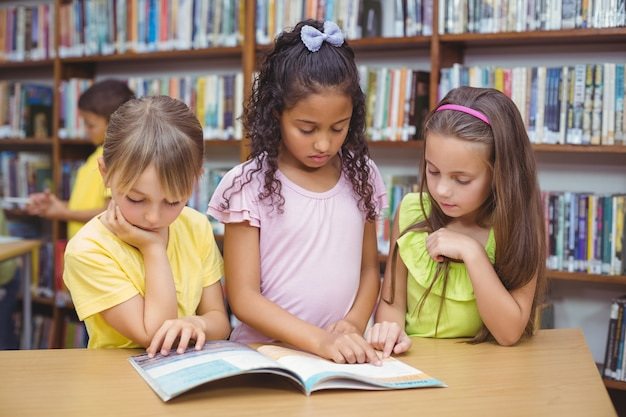 Pupils reading book together in library