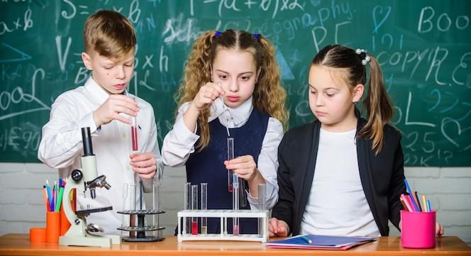 Gli alunni studiano chimica a scuola i bambini si divertono con gli esperimenti chimici la sostanza chimica si dissolve