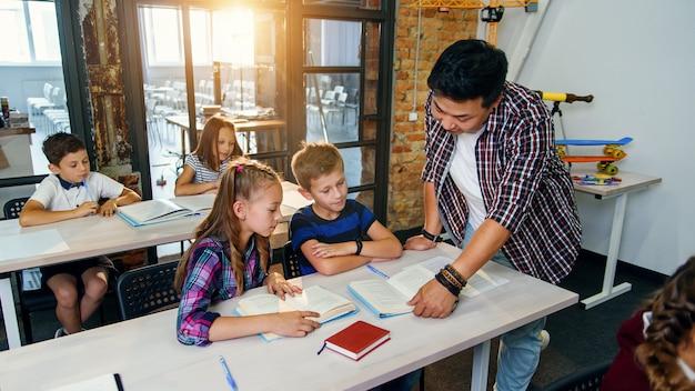 Ученики с молодым корейским учителем с улыбкой смотрят на учебник, обсуждают домашнее задание на уроке в начальной школе.