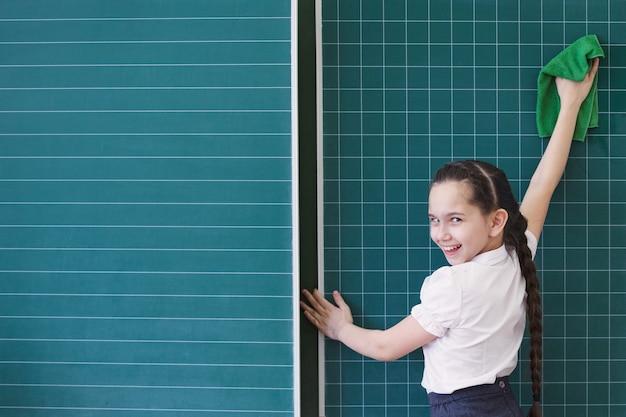 生徒は黒板のチョーク番号に書き込み、数学的なタスクを解決します