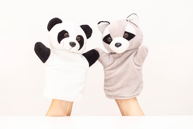Puppet theater on a white background. friendly animals hold hands. the concept of playing with children, friendship, family, entertainment. nanny entertains children. copyspace