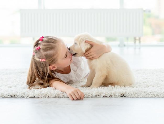 Puppy kissing little girl